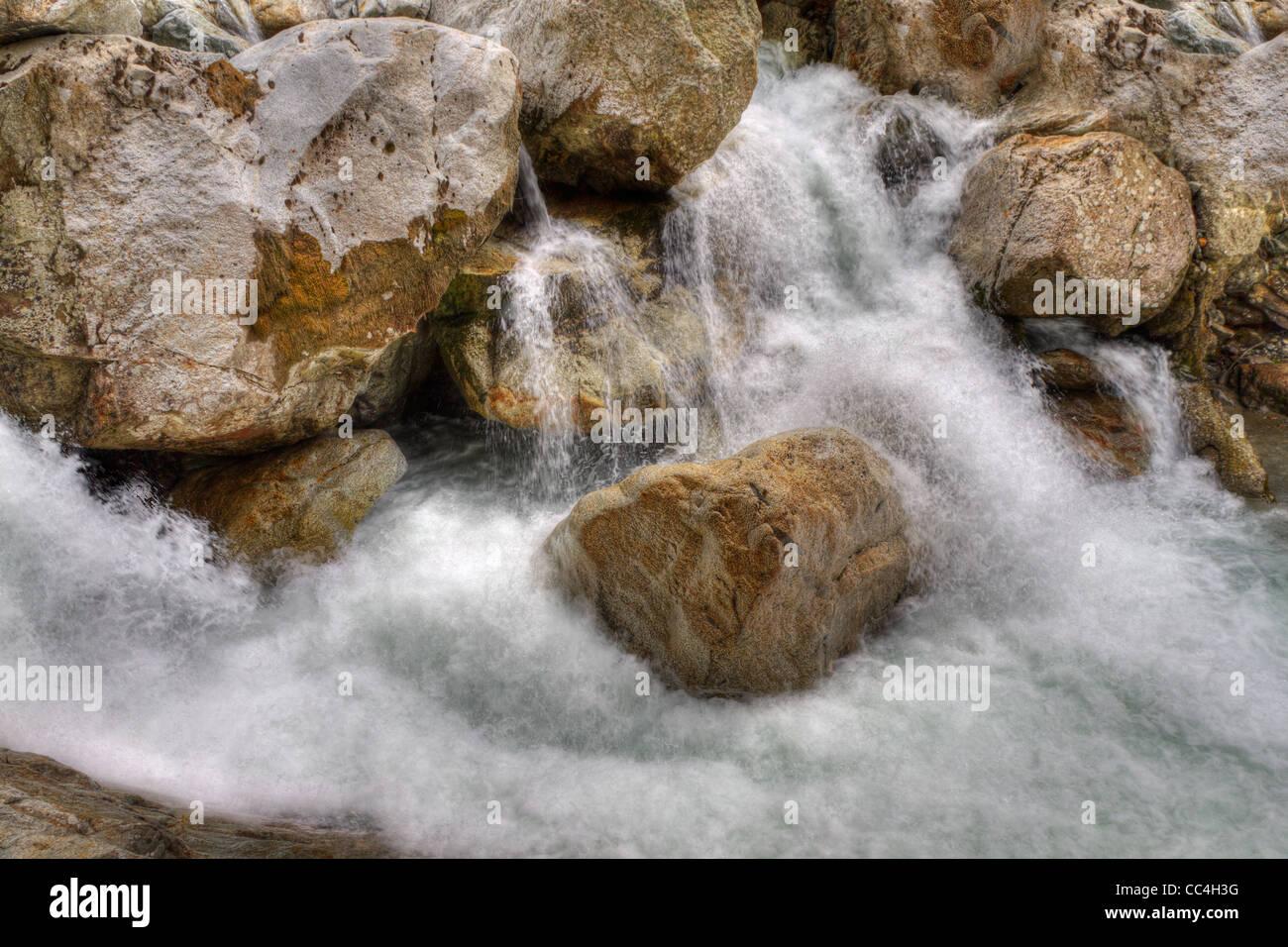mountain stream gushing down as white water over rocks - Stock Image