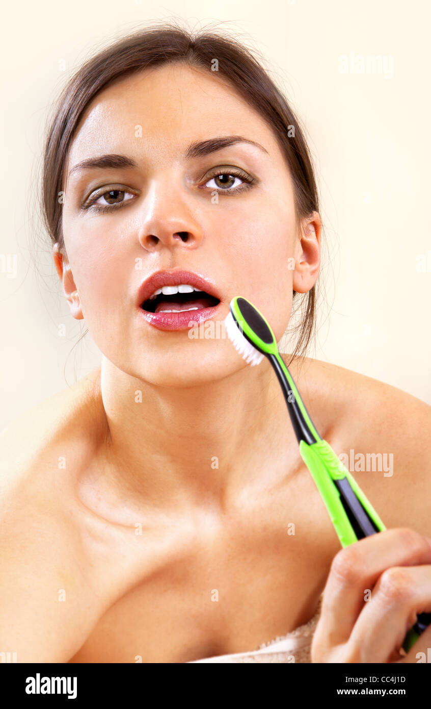 beautiful woman with tooth-brush cleans her teeth - Stock Image