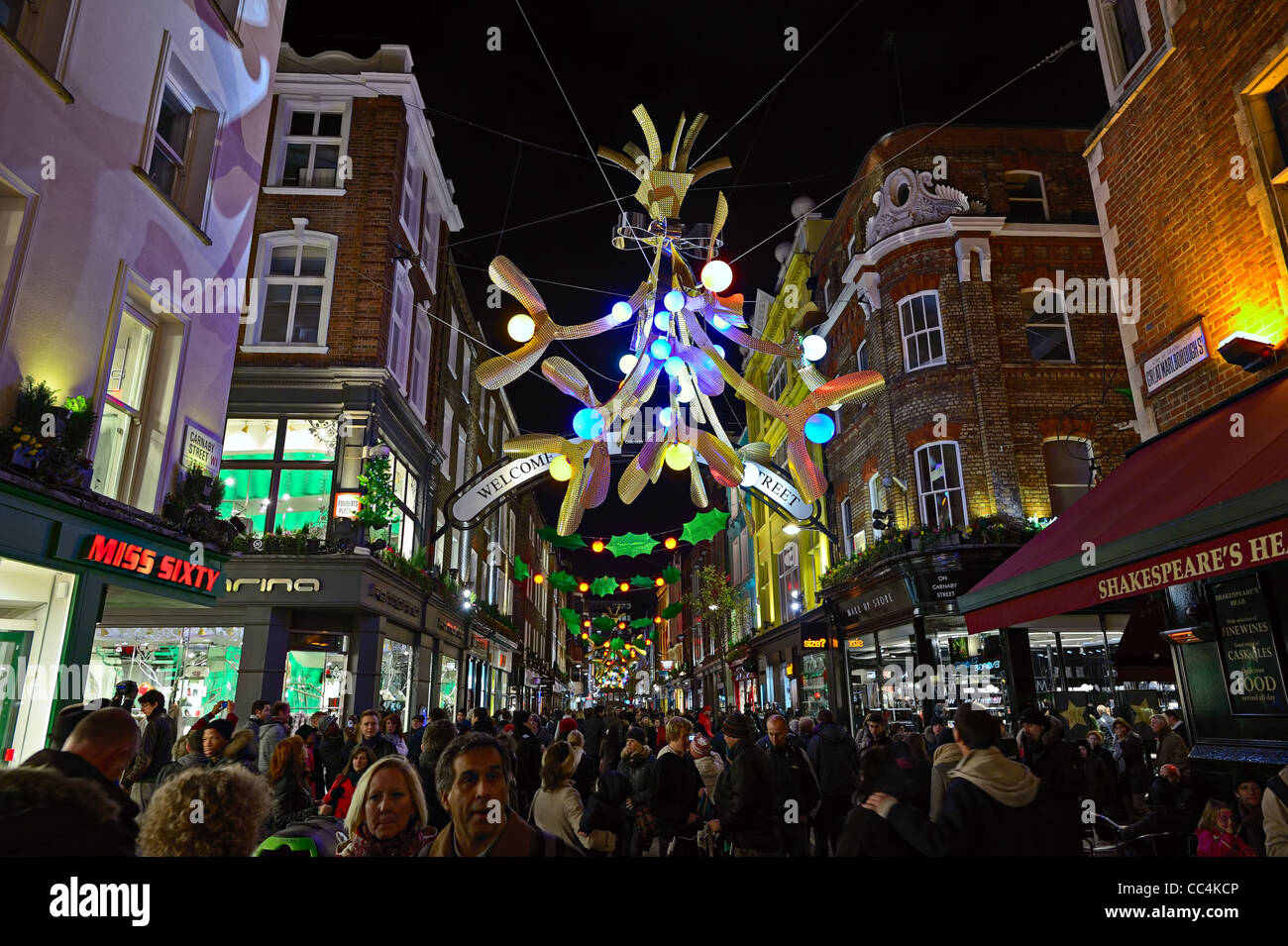 Carnaby Street full of Christmas shoppers, London, England, UK, with festive decorative lights at night - Stock Image