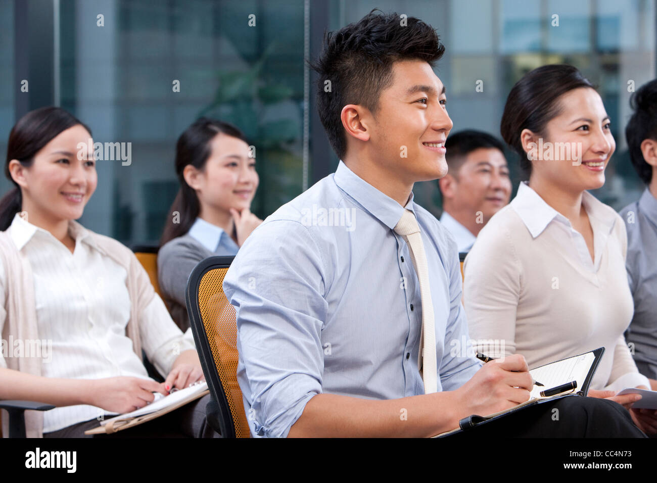 Businesspeople happily listening to a lecture - Stock Image