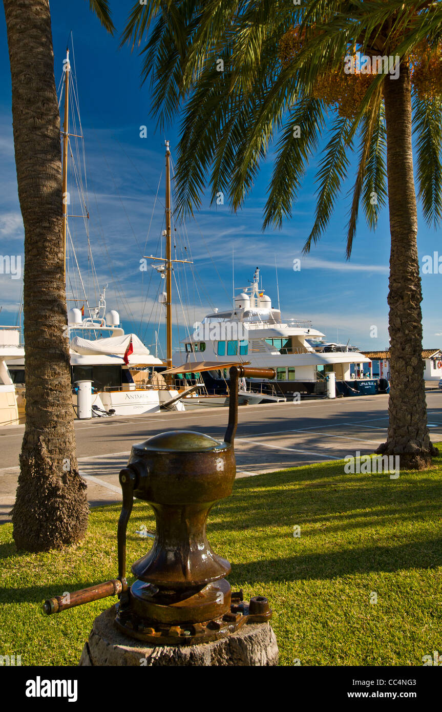Historic  anchor capstan in foreground with luxury yachts moored behind at Puerto Portals Mallorca Spain - Stock Image