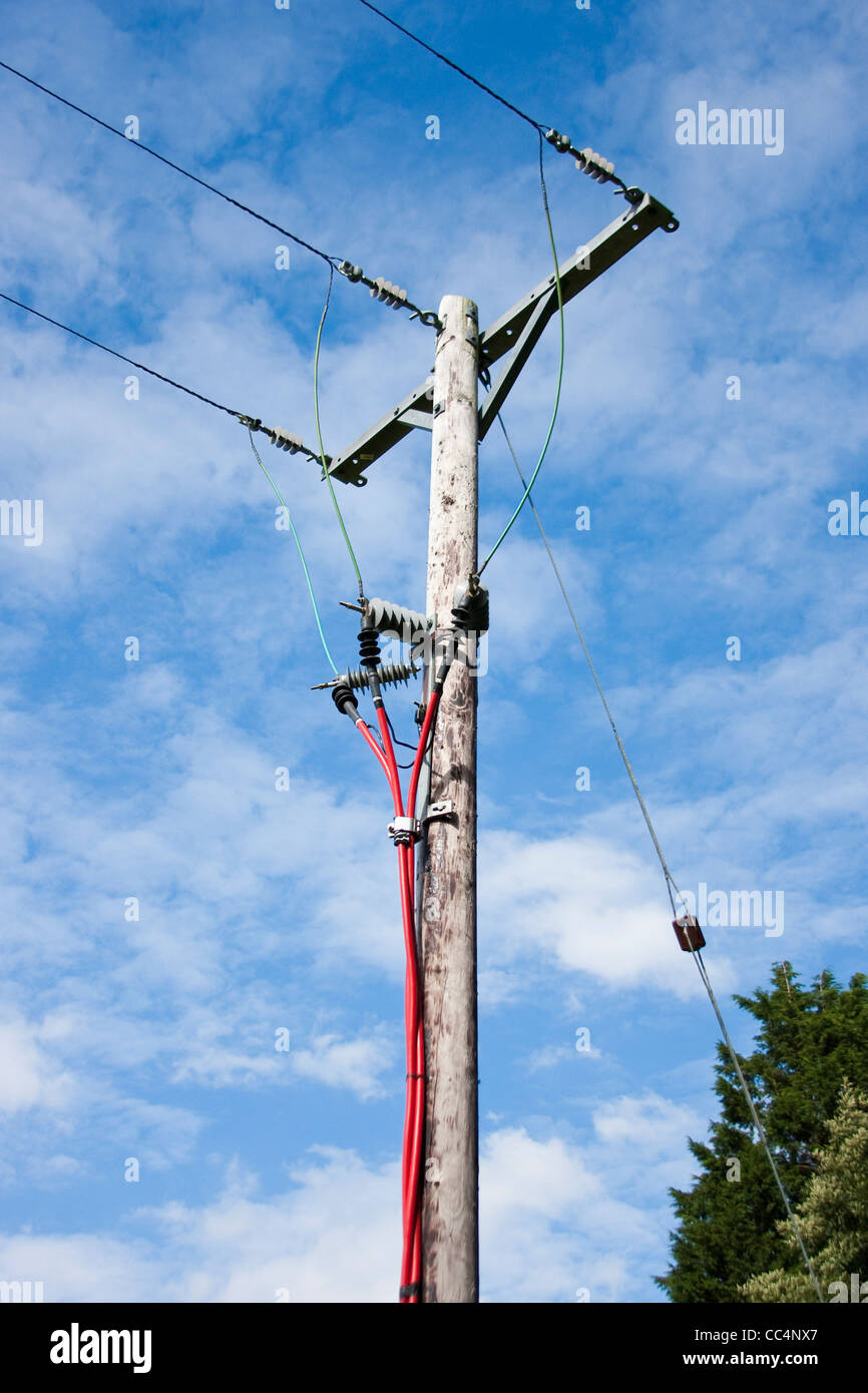 Electricity Pole With Bright Red and Overhead Cables against Blue Sky - Stock Image