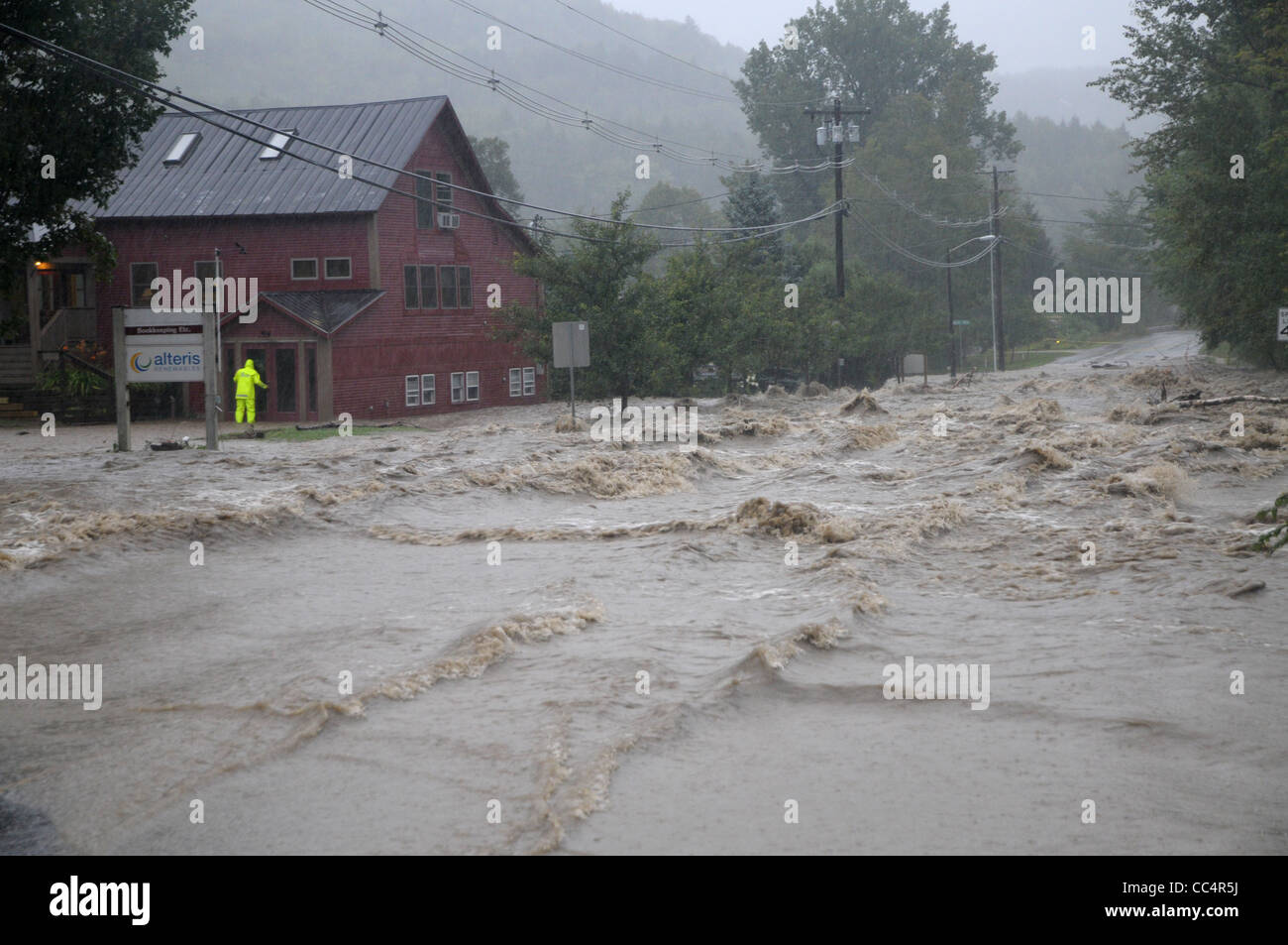 A rescuer searches a building as raging waters caused by tropical storm Irene flood Waitsfield, VT Stock Photo