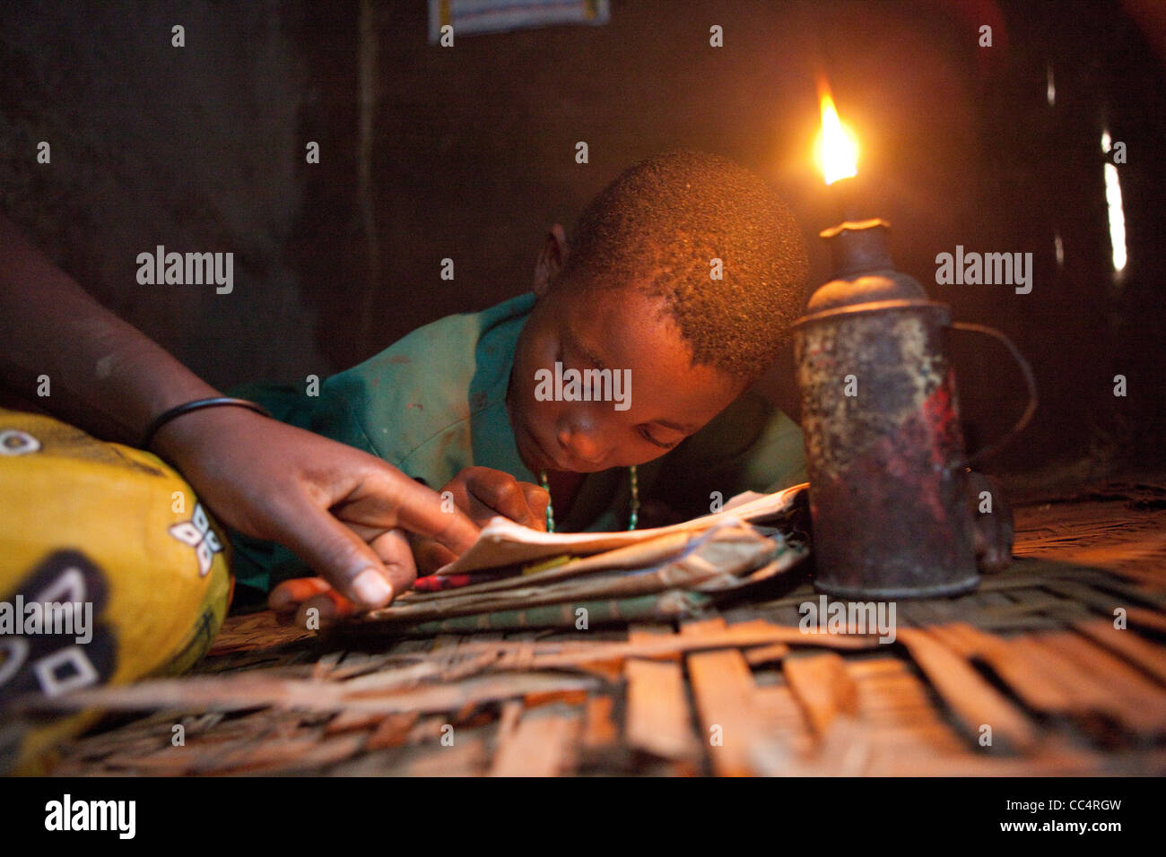 A student studies by the light of a kerosene lamp in Masaka, Uganda, East Africa. - Stock Image