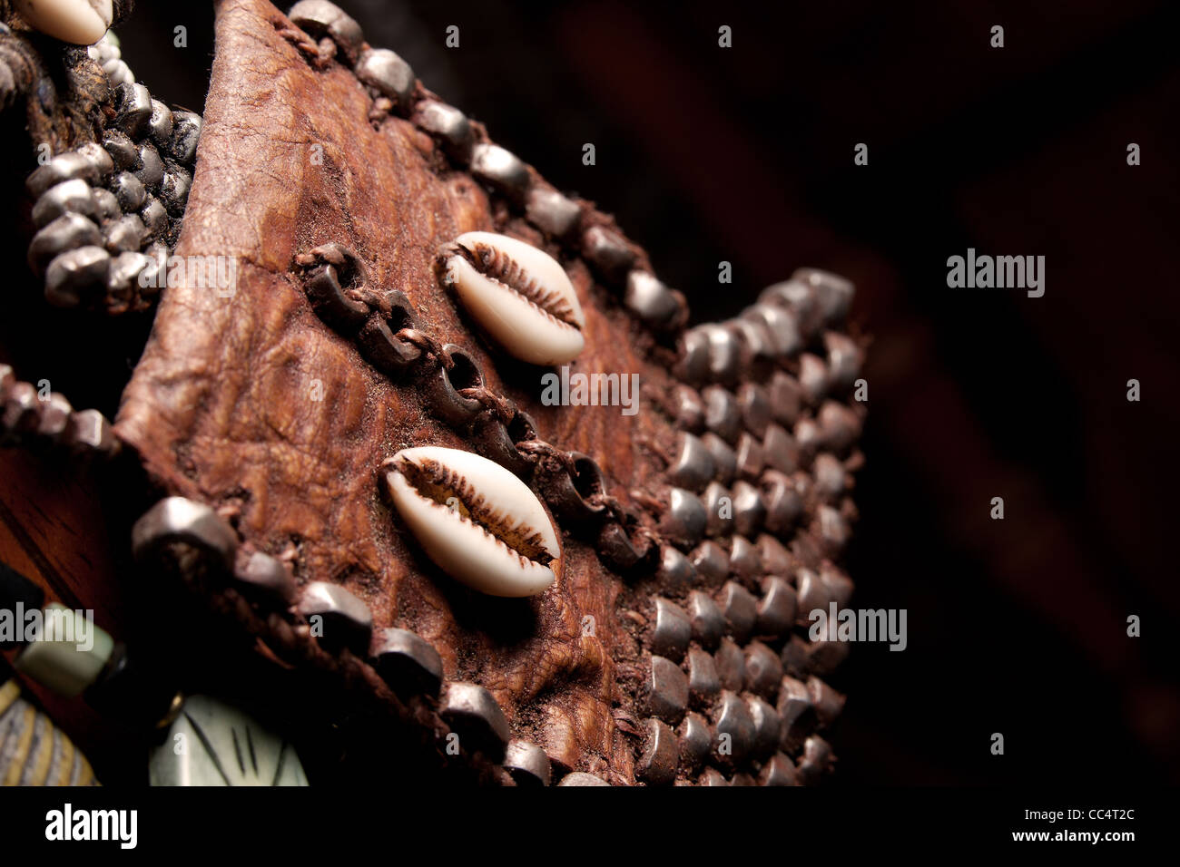 natural African tribal cowrie shell beads and leather pouch in market with a black background. - Stock Image