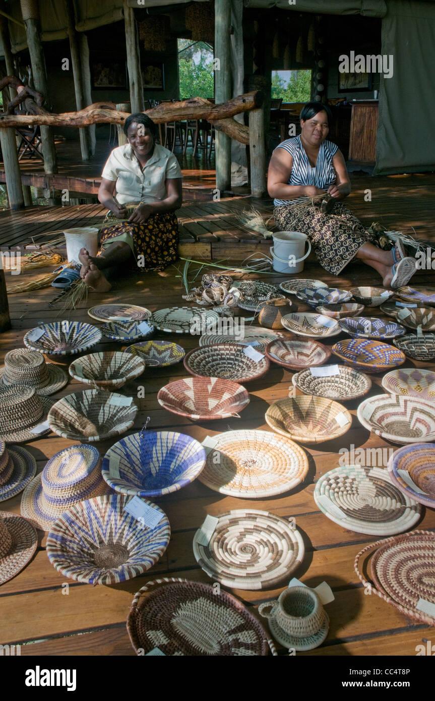Africa Botswana Tuba Tree-Women weaving baskets, showing baskets in foreground - Stock Image