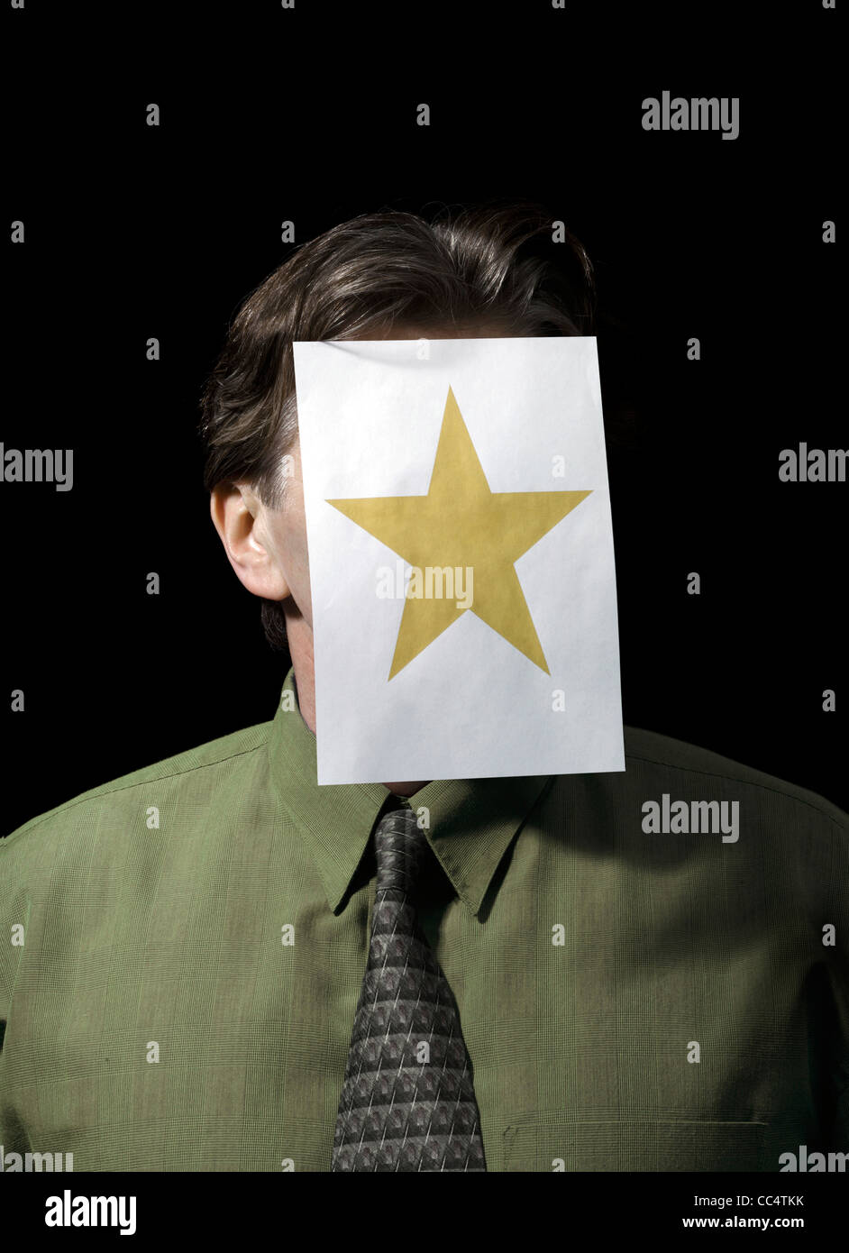 Studio shot of a Portrait of a Businessman with Paper star on Face - Stock Image