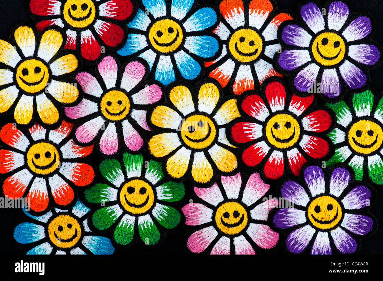 Embroidery iron on patches of Multicoloured smiley face flowers on a black background - Stock Image