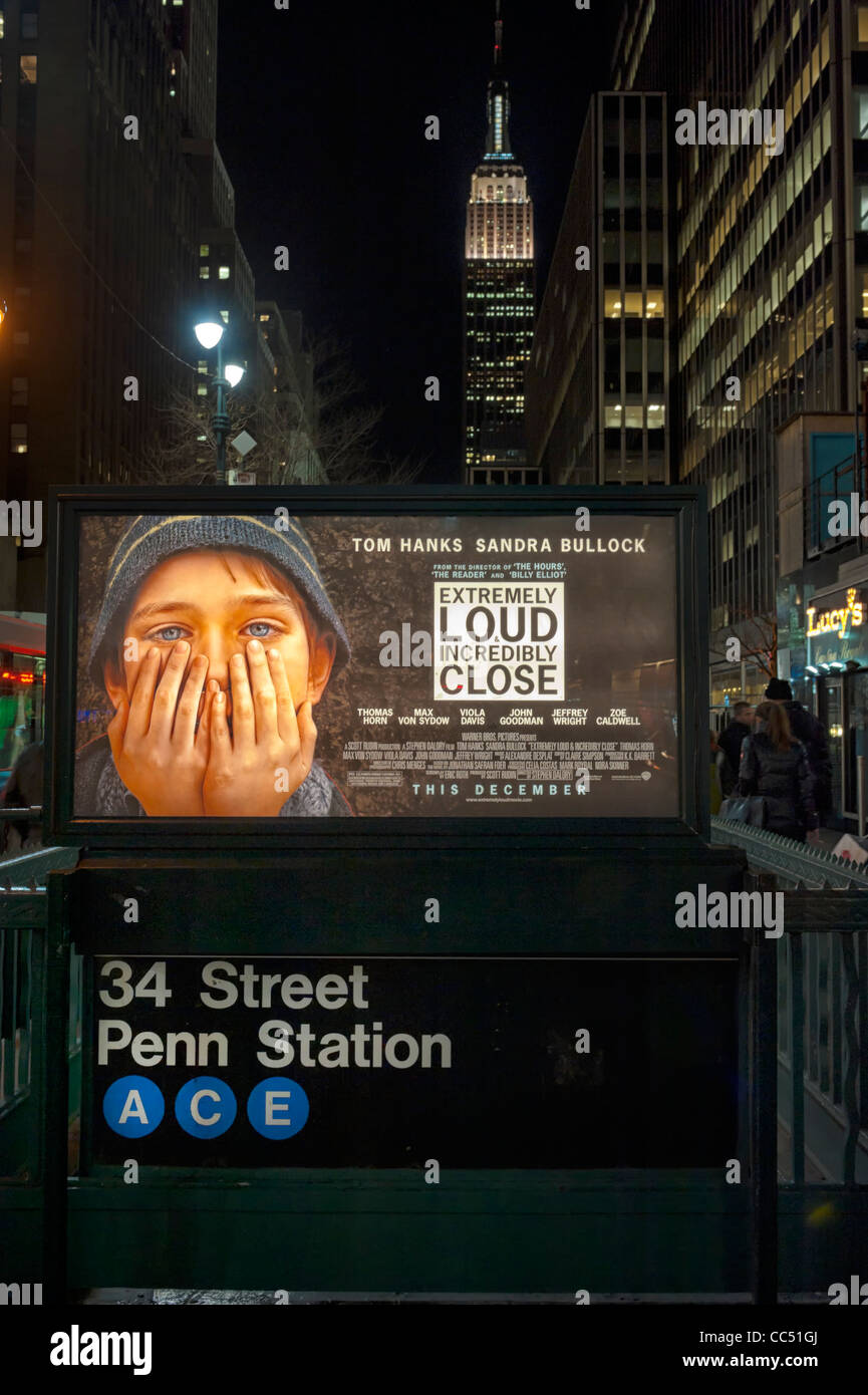 Movie poster 'Extremely Loud & Incredibly Close' over subway entrance, with Empire State Building, Manhattan - Stock Image