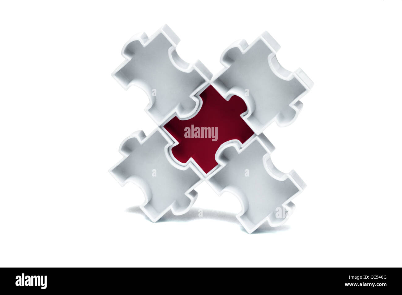 Red jigsaw puzzle interlocked in the centre with white pieces - Stock Image