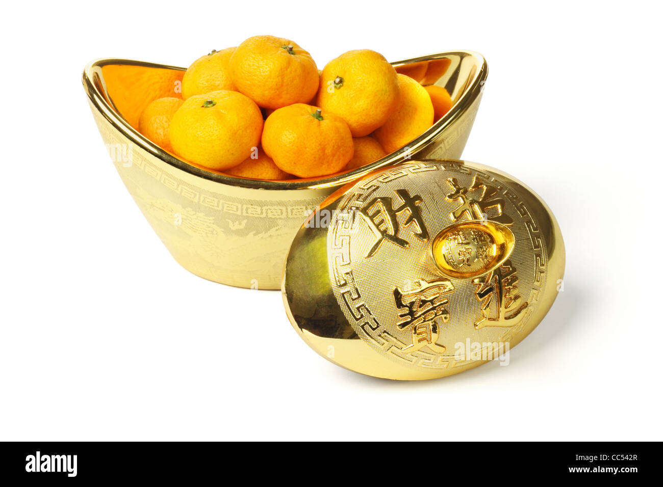Mandarin oranges in gold ingot container on white background - Stock Image