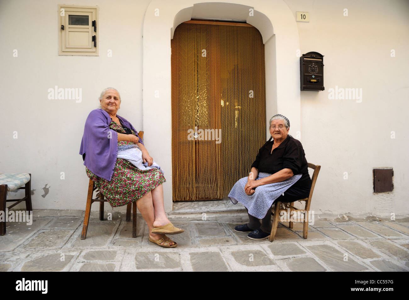italy, basilicata, roccanova, old italian women outside house - Stock Image