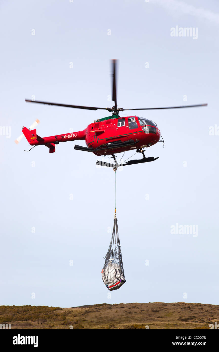 Red Helicopter carrying in a net; Cornwall; UK - Stock Image