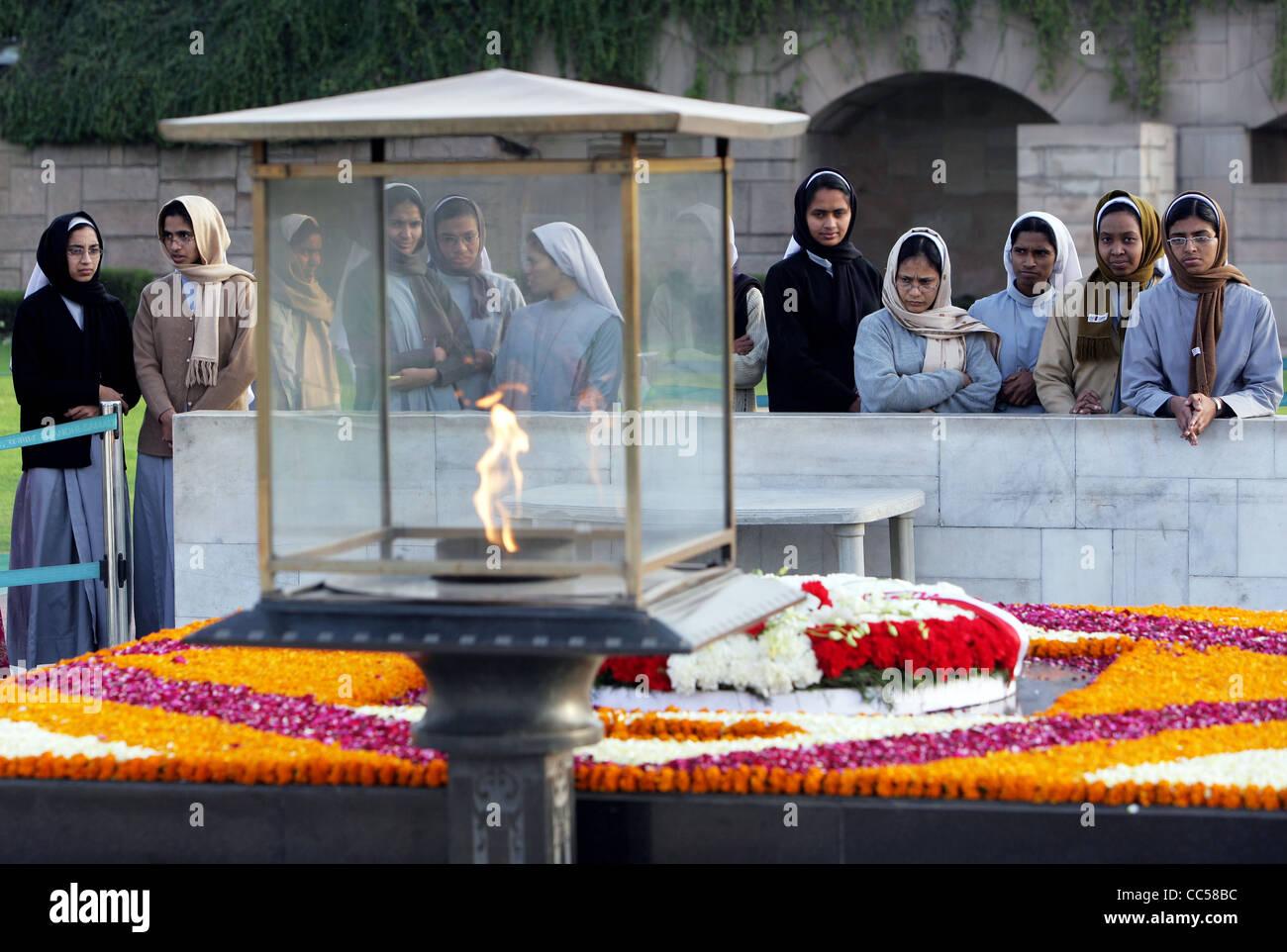 India, New Delhi: Catholic nuns commemorate Mahatma Gandhi at his grave site memorial cremation ghat in New Delhi - Stock Image