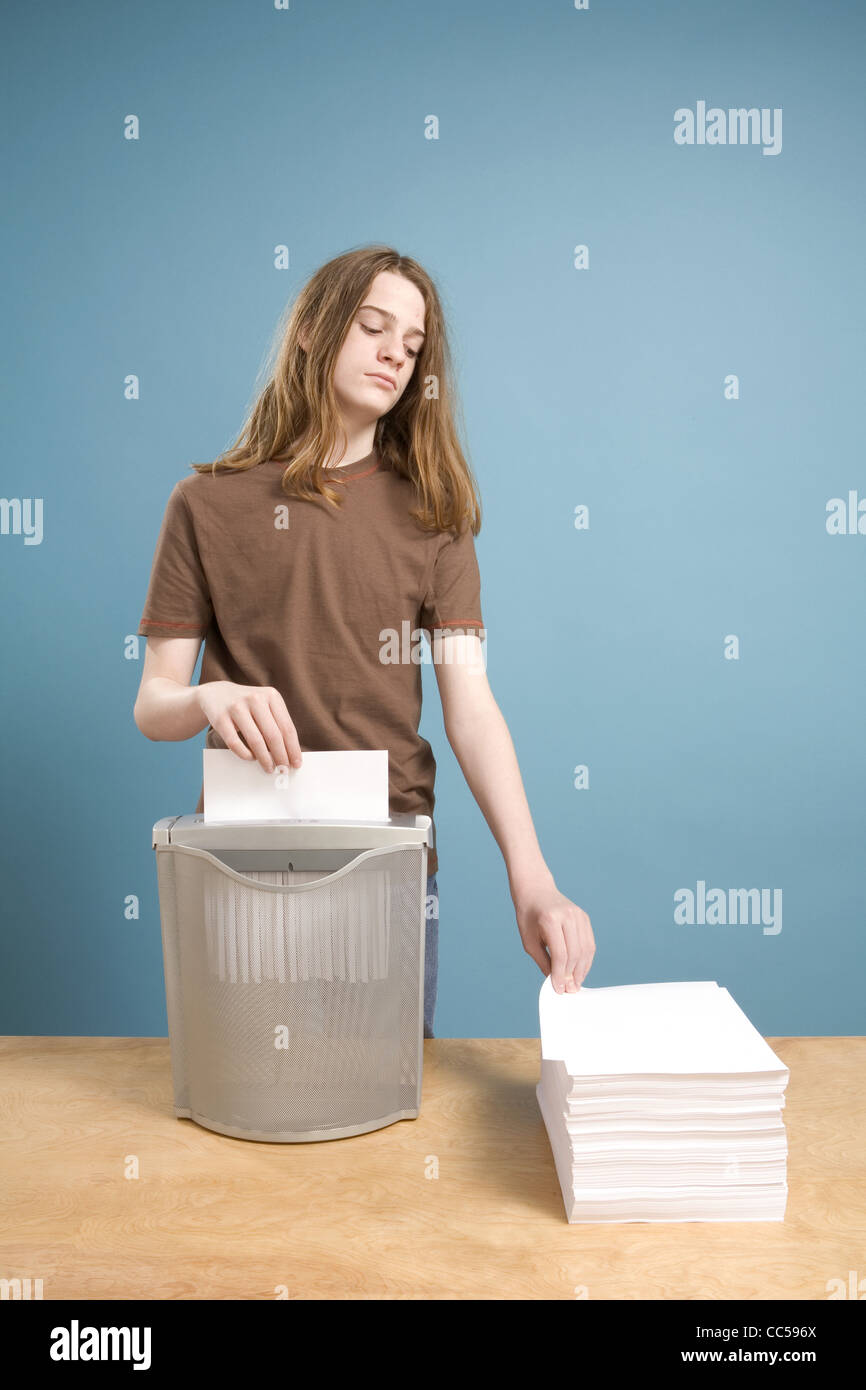 Teen Boy in Act of Shredding Blank Paper - Stock Image