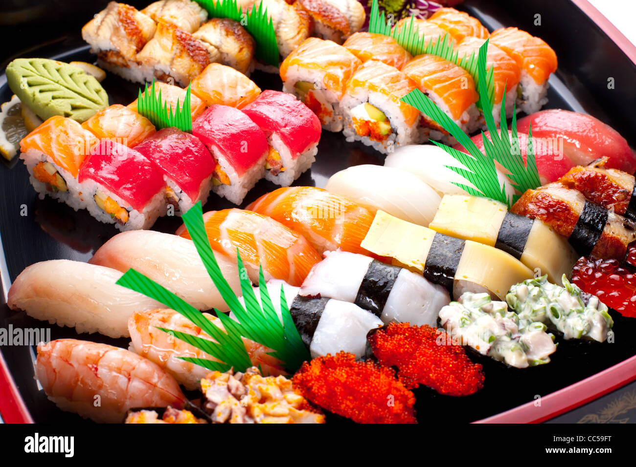 Sushi rolls on a black plate. - Stock Image