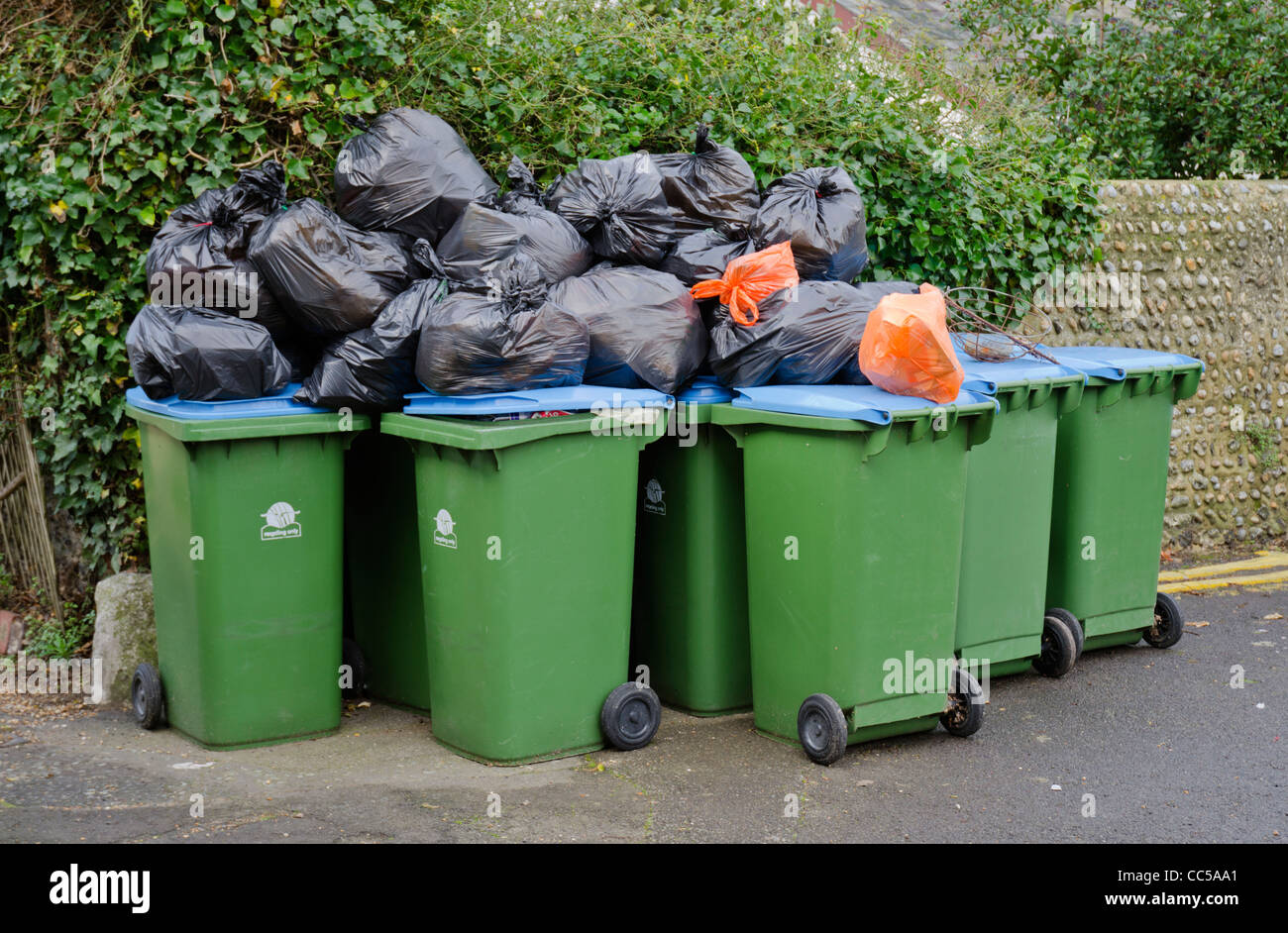 Rubbish bags and recycling wheelie bins awaiting collection in England, UK. - Stock Image