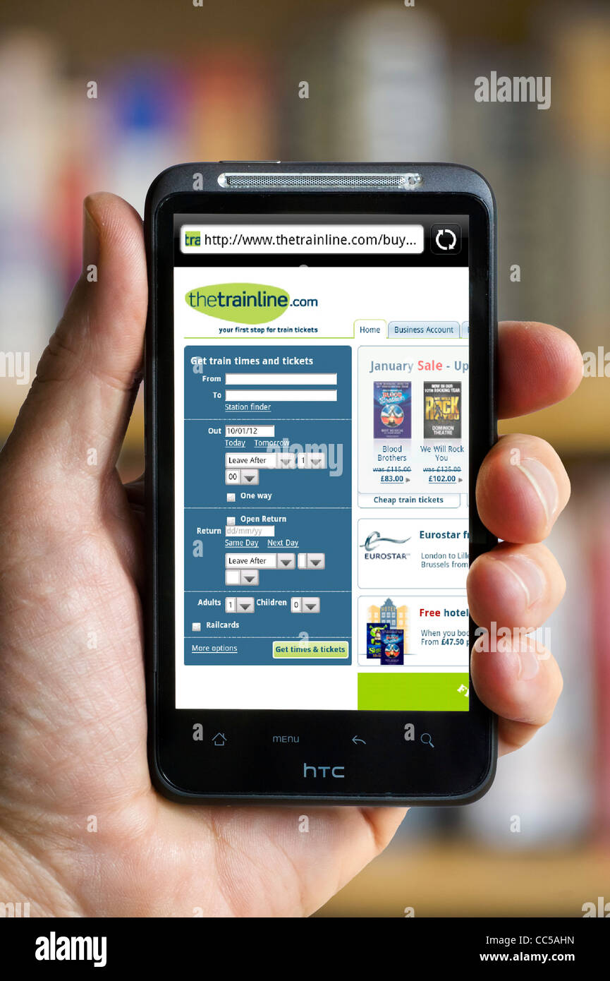 Booking train tickets on thetrainline.com website HTC smartphone - Stock Image