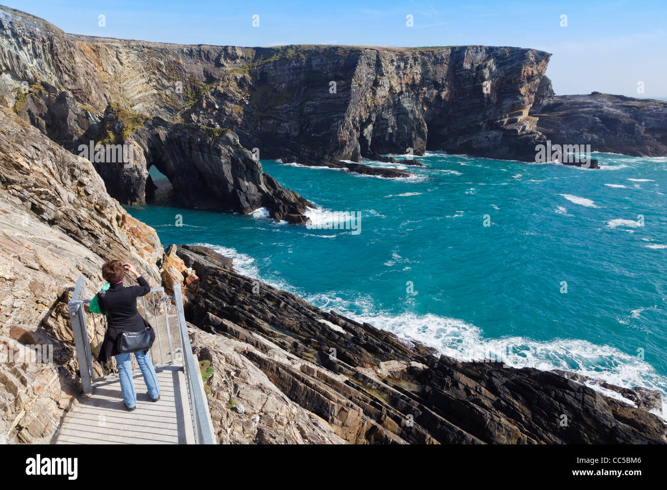 Woman taking photographs of Mizen Head, County Cork, Republic of Ireland. - Stock Image