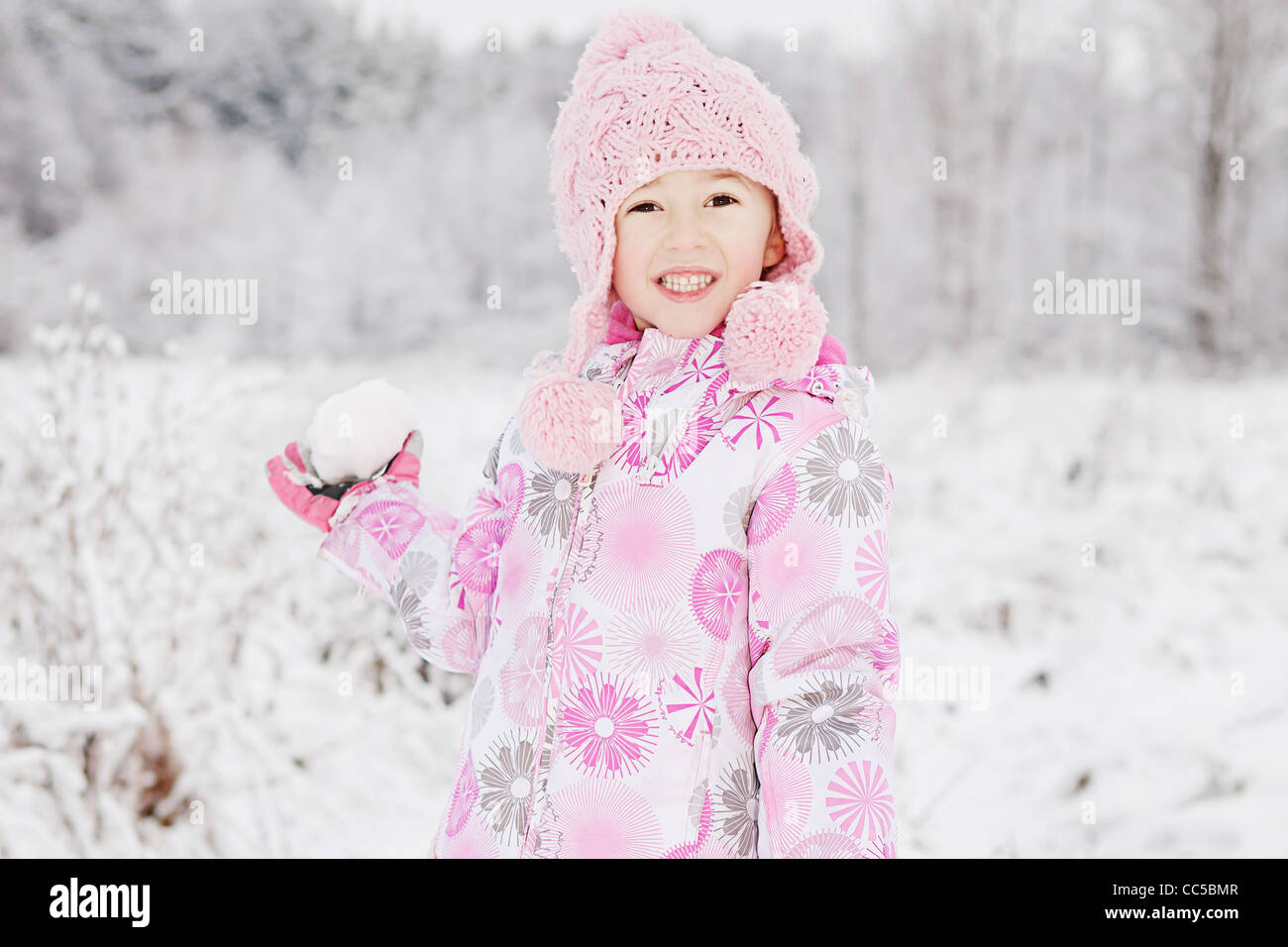 a portrait of a girl with a snowball - Stock Image