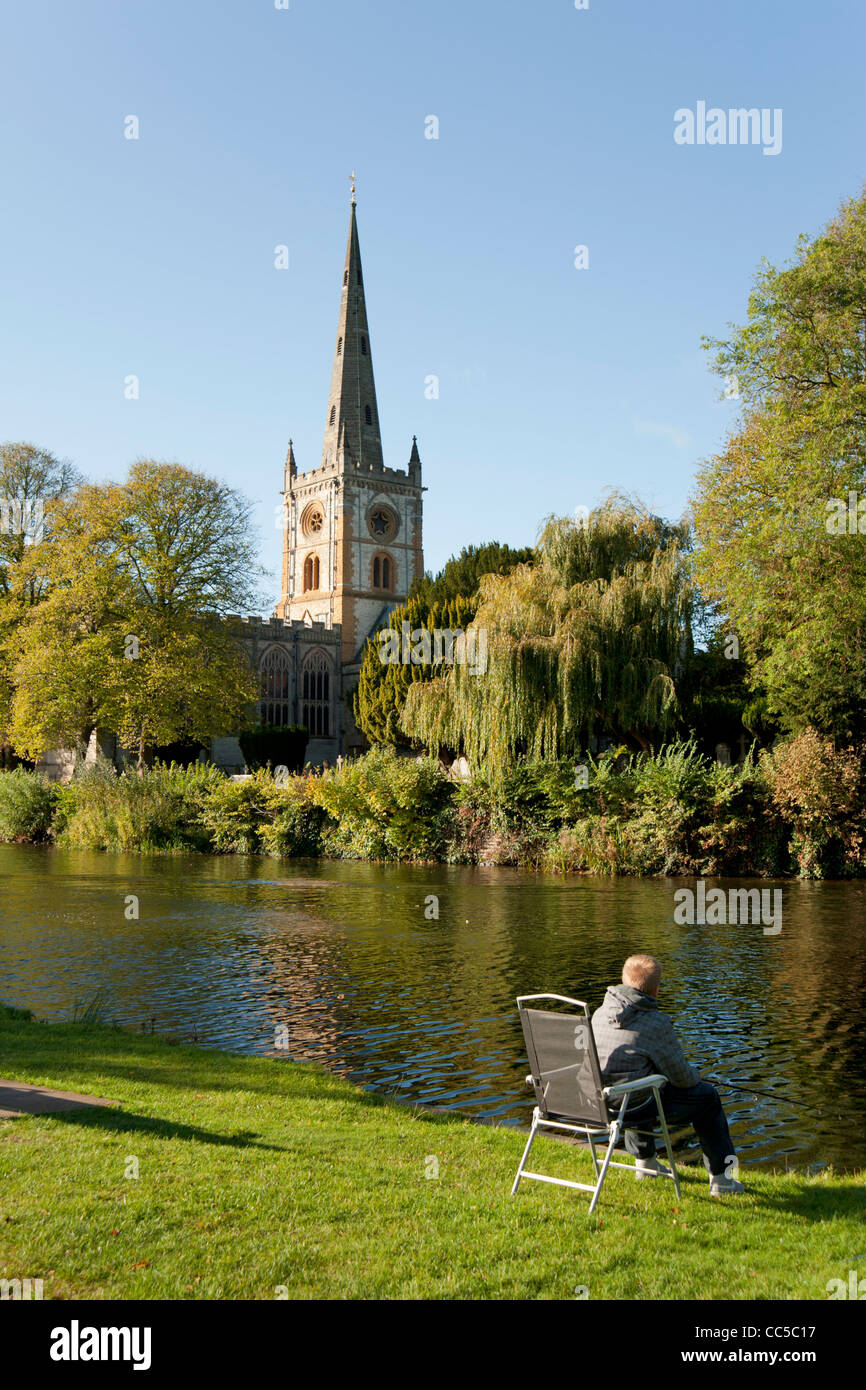 A boy fishing on the banks of the river Avon opposite Holy Trinity Church, Stratford-upon-Avon, Warwickshire, England, - Stock Image