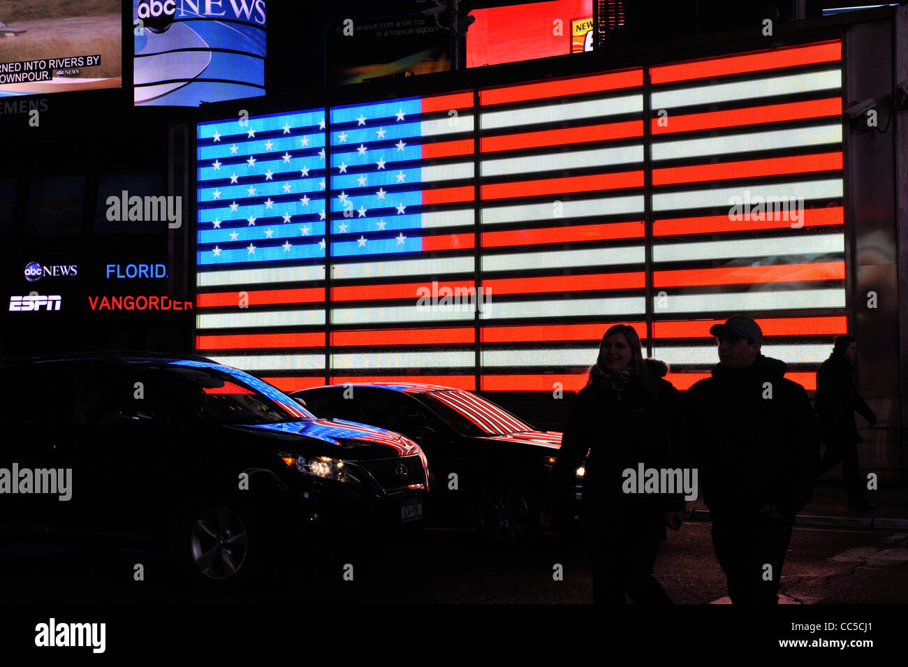 Times Square, electric American Flag of U.S. Armed Forces Career Center, people silhouetted in Manhattan, New York Stock Photo