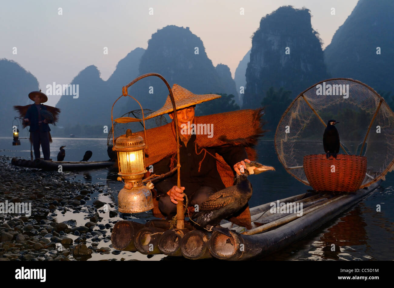 Chinese fishermen with cormorants at dawn on the Li river and tall karst formation mountains Yangshuo China - Stock Image
