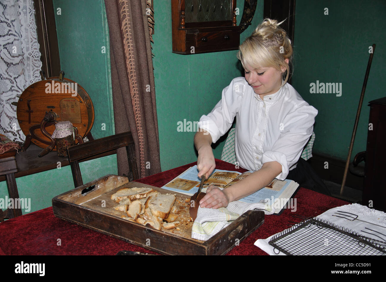 Young woman making bread in pit cottage, Beamish, The North of England Open Air Museum, County Durham, England, - Stock Image