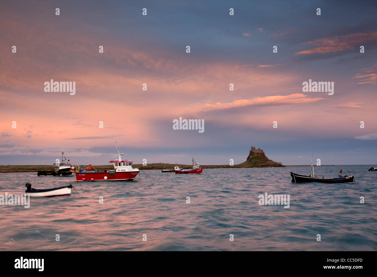 Sunset afterglow over Lindisfarne Castle and harbour. - Stock Image