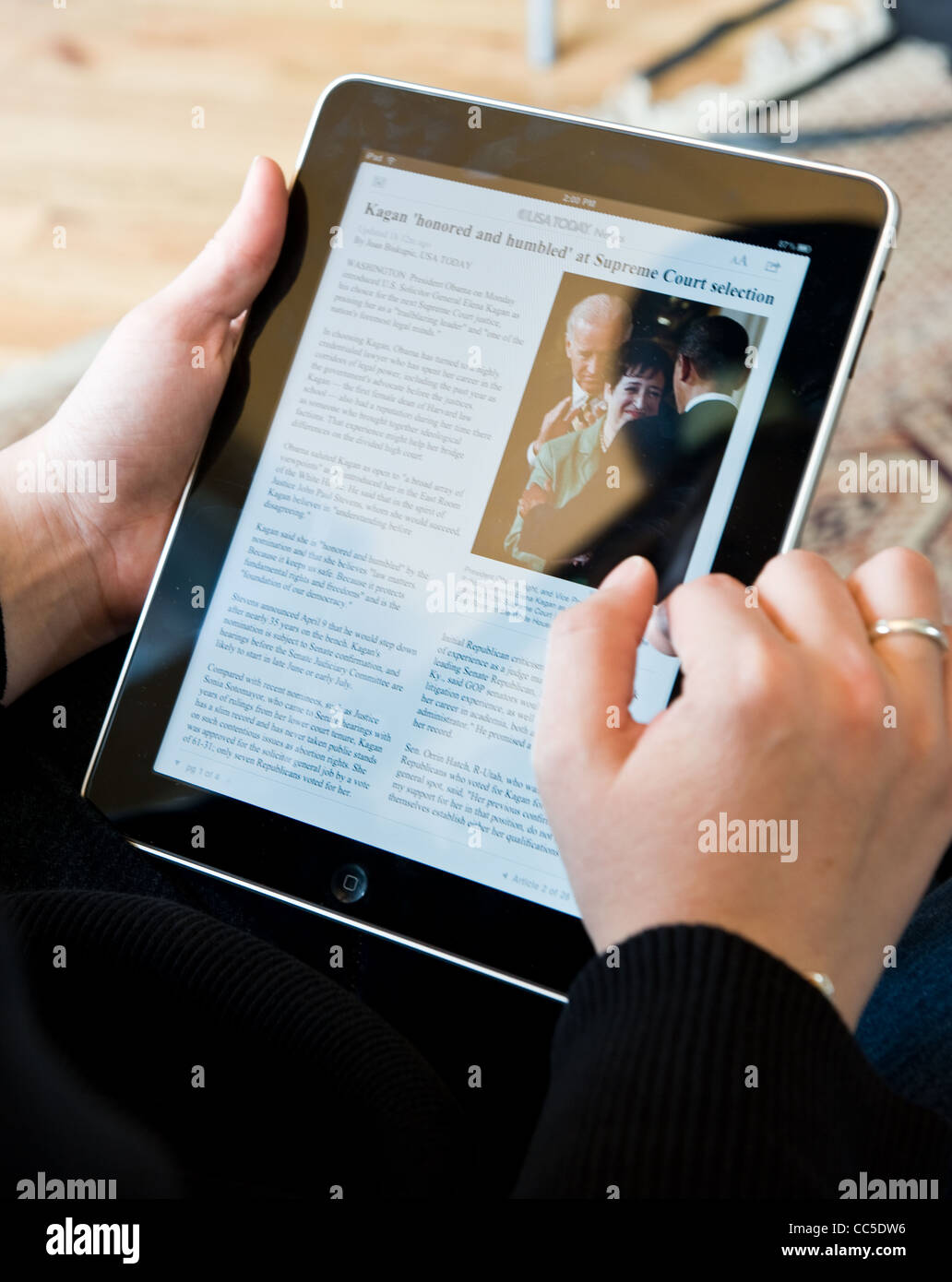 Caucasian woman uses Apple iPad to read USA Today news article - Stock Image