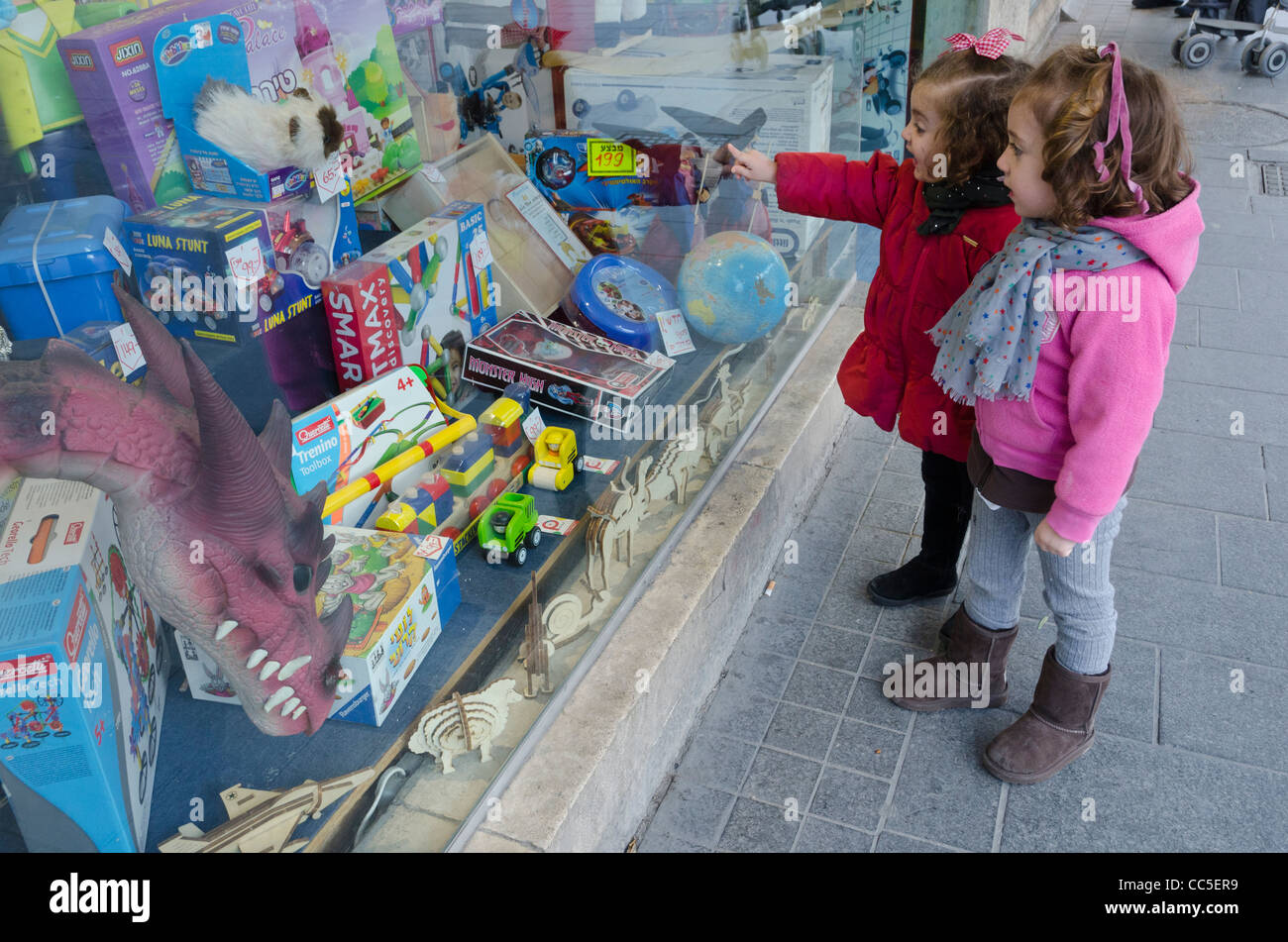 two young girls admiring the shopwindow of a toy shop. jaffa Road. Jerusalem. israel - Stock Image