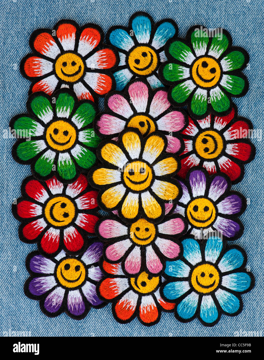 Embroidery iron on patches of Multicoloured smiley face flowers on a denim jean background - Stock Image