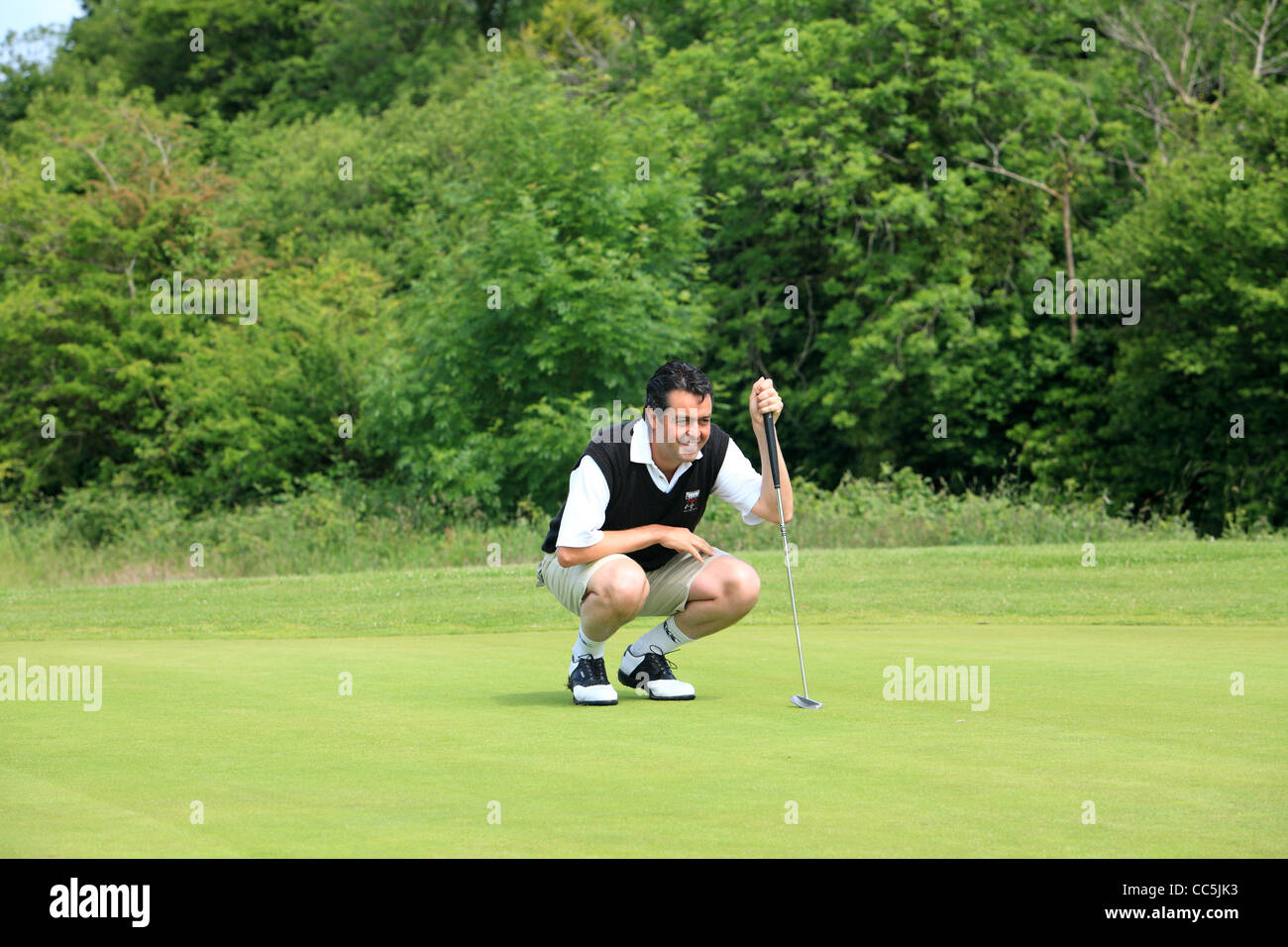 Golfer lining up his putt on the green - Stock Image