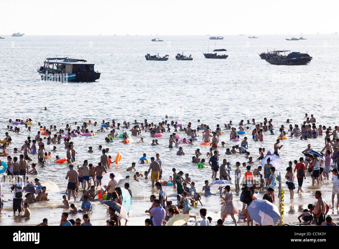 People swimming in the South China Sea, Silver Beach, Beihai, Guangxi , China - Stock Image