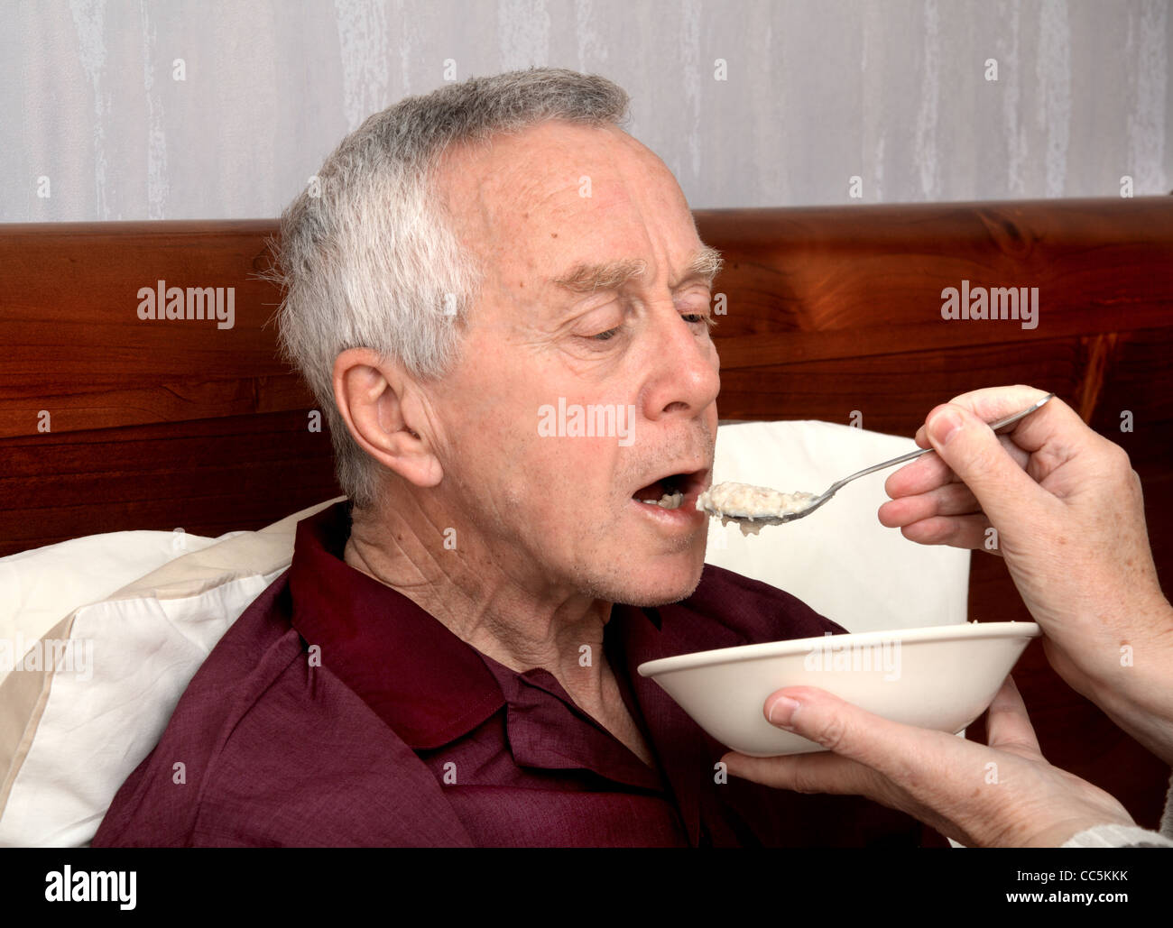 A bedbound man in his 60's being fed by his wife/carer - Stock Image