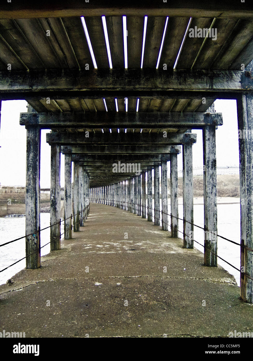 Weathered wooden beams on underneath of harbour pier at Whitby, North Yorkshire, UK. - Stock Image