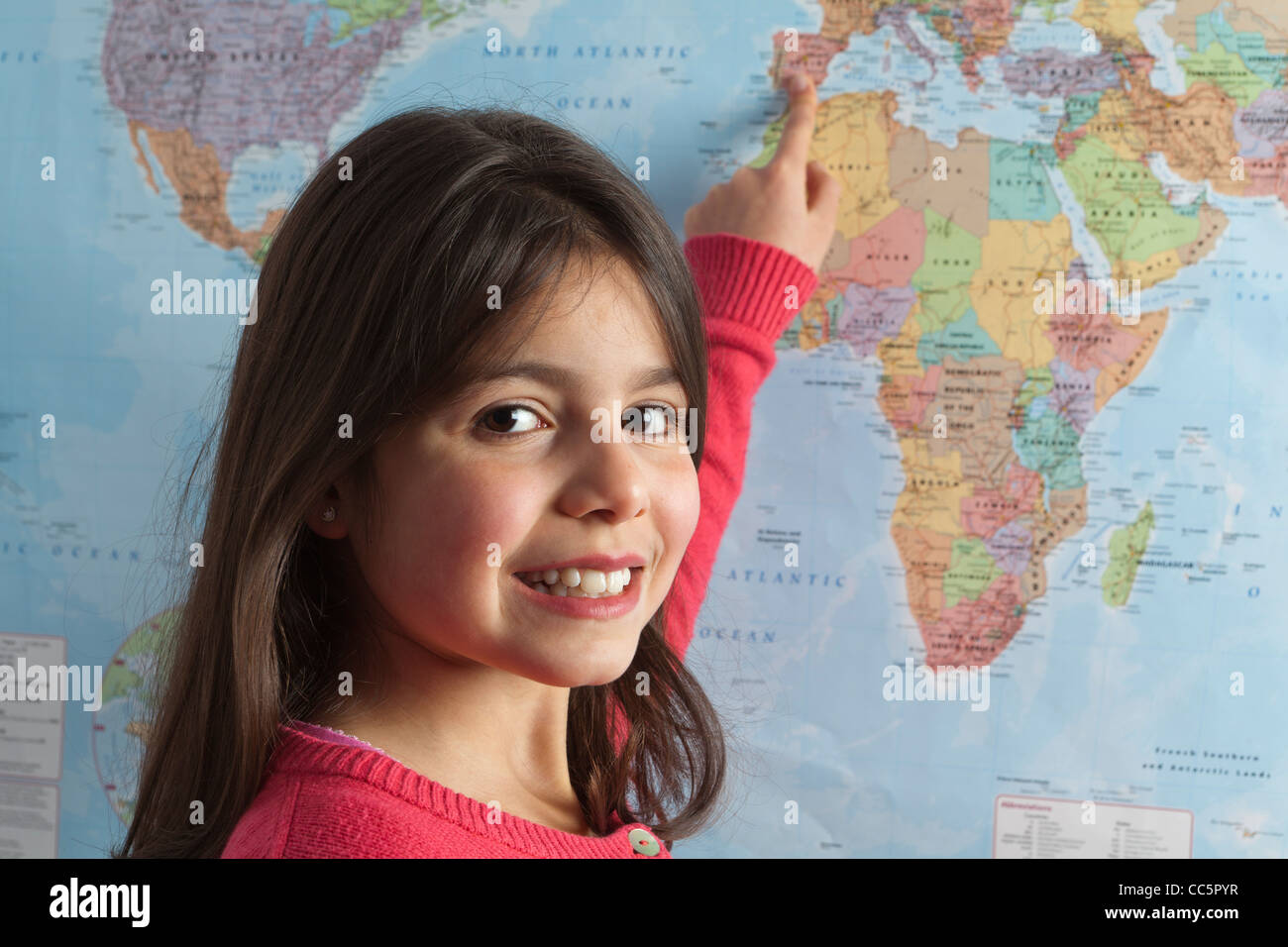 Young girl pointing to different countries on the world map Stock Photo
