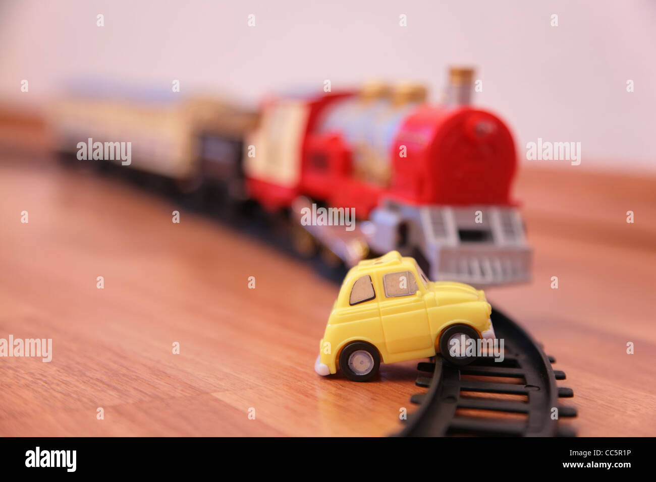 Red toy train and yellow toy car on railroad Stock Photo