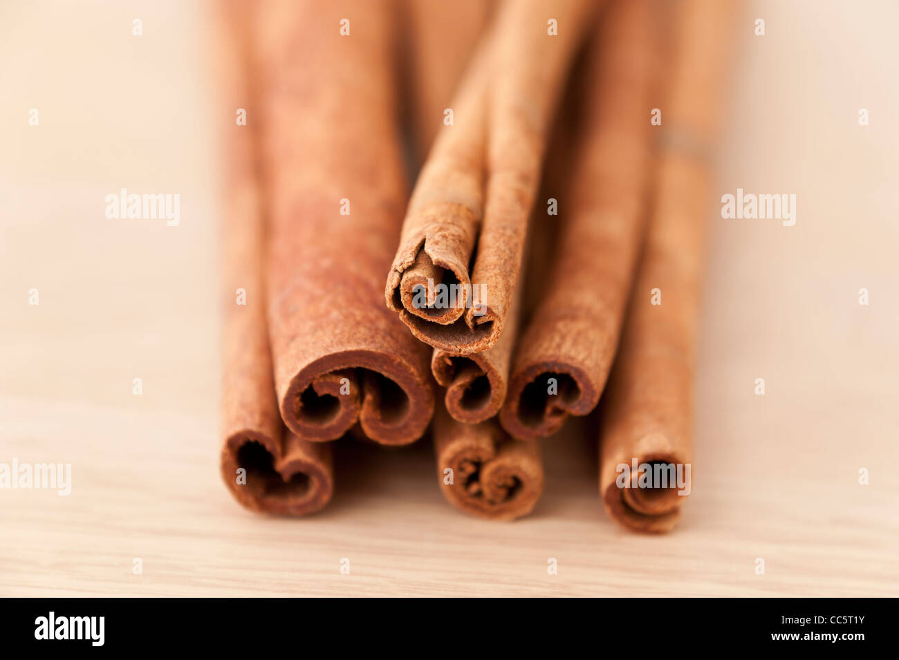 Pile of Cinnamon sticks on a wooden surface - Stock Image