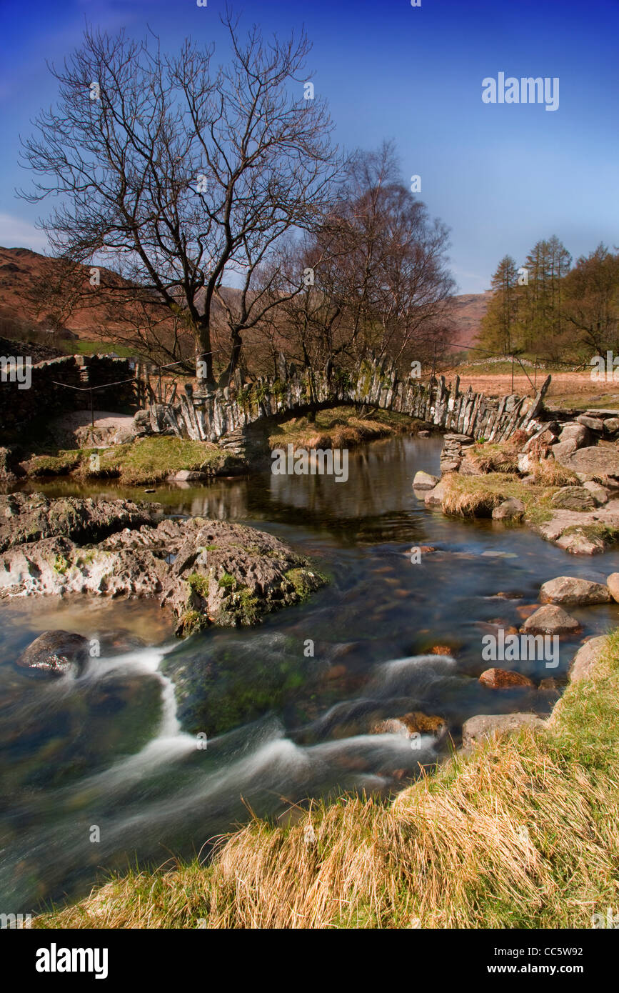Slater Bridge crosses the River Brathay on its way from Little Langdale Tarn to Elterwater and is a typical pack Stock Photo