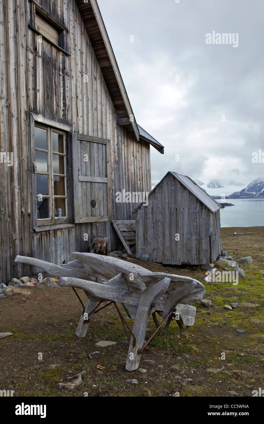Old wooden trapper's hut and wheelbarrow, Camp Mansfield, Blomstrandhalvoya, Spitzbergen, Svalbard, Arctic Norway, - Stock Image