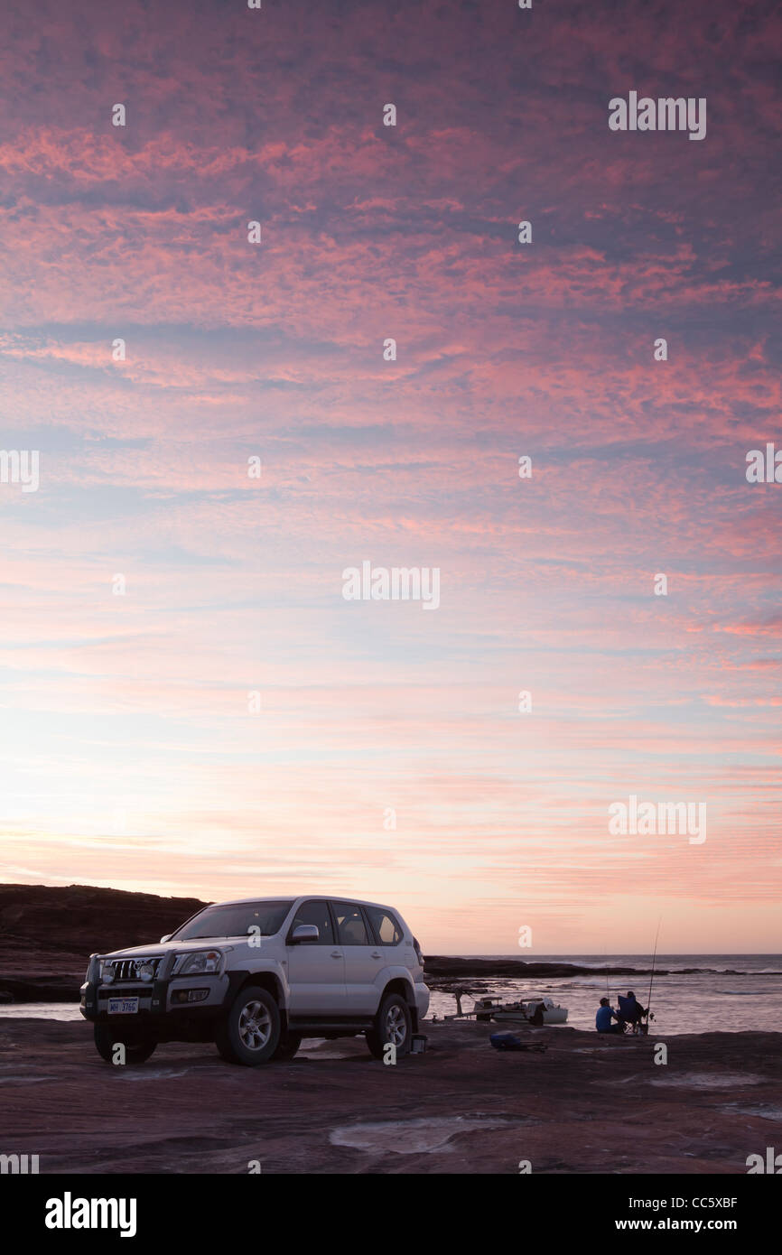 Toyota Landcruiser pulled up on Red Bluff Beach against a stunning sunset. - Stock Image