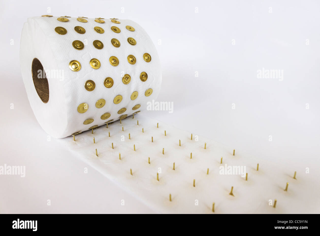 a roll of toilet paper pierced by thumbtacks with white background