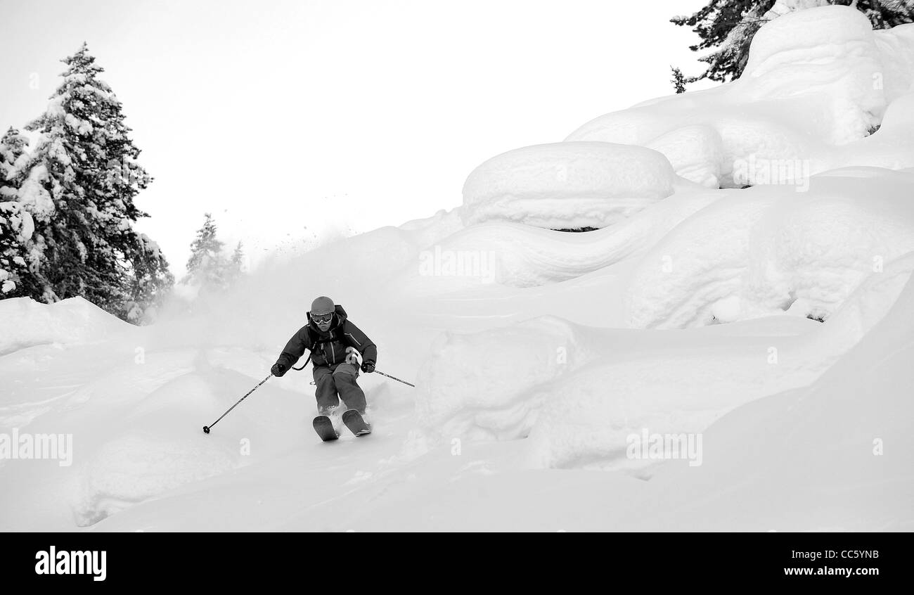 A skier jumps down snow covered rocks off piste in the French ski resort of Courchevel on Christmas Day. - Stock Image