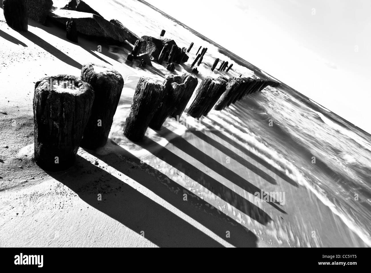 Breakwaters on the beach in Niechorze. - Stock Image