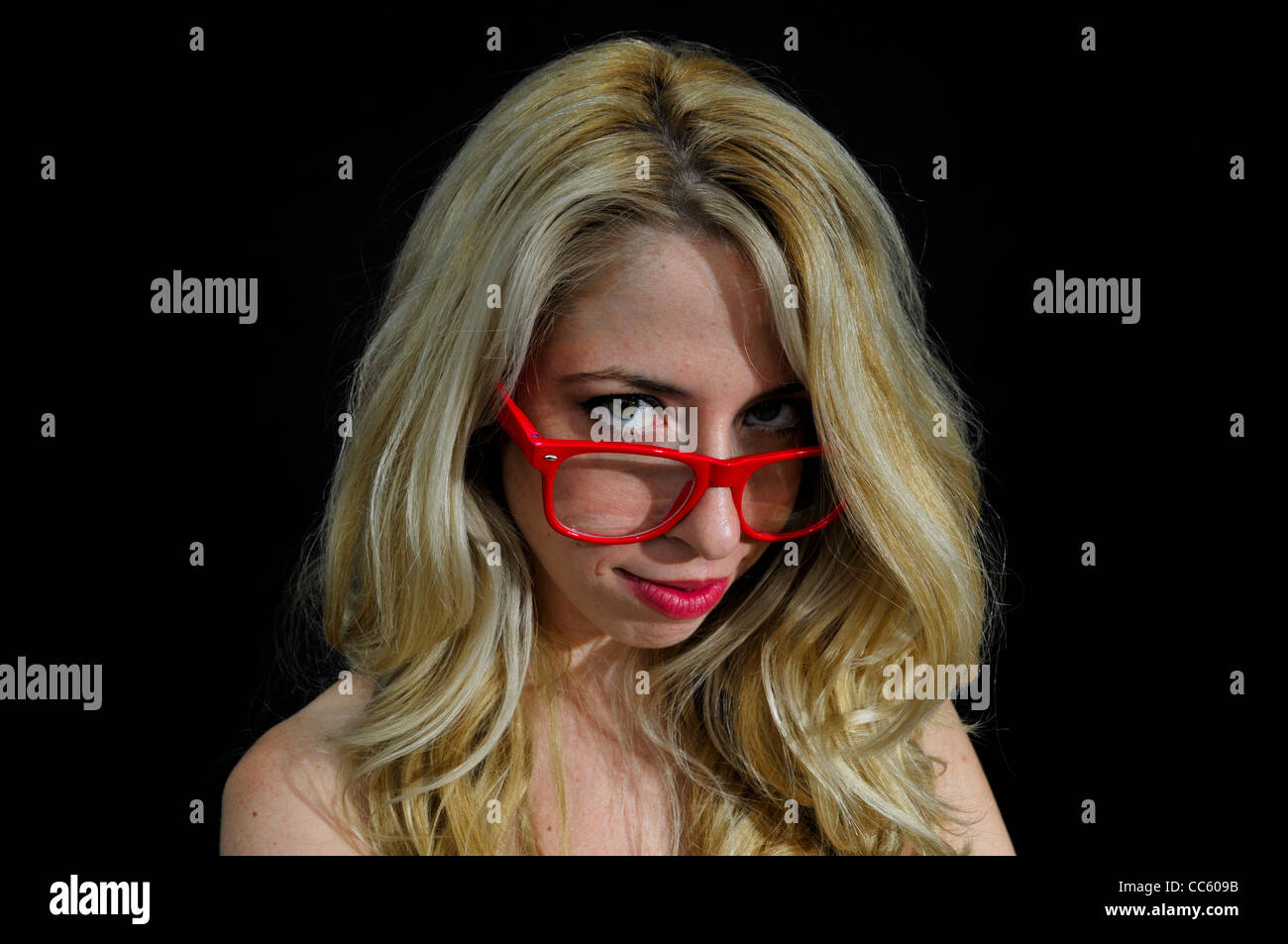 Intelligent blond woman with red glasses on black background - Stock Image