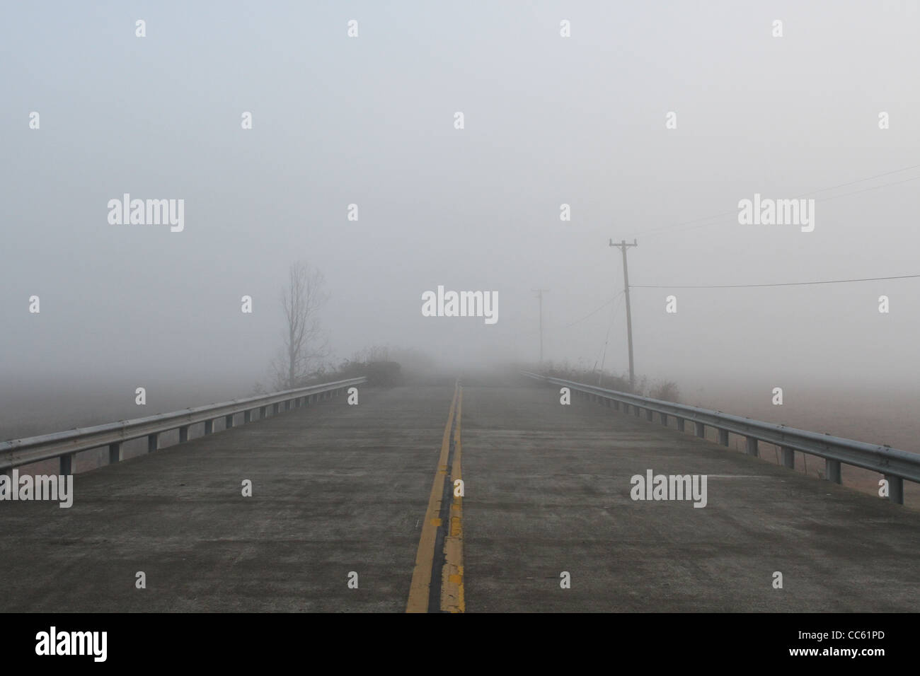 A road in fog seemingly leading to nowhere. - Stock Image