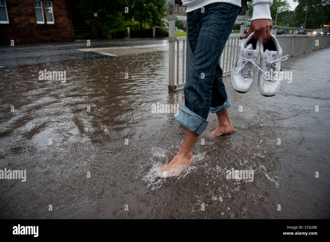 a passer by carries there shoes through a flooded part of town after