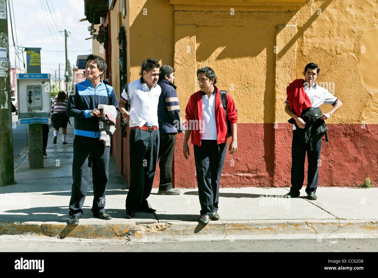 group of good humored teenage Mexican high school boys standing on street corner after school in front of colorful Stock Photo