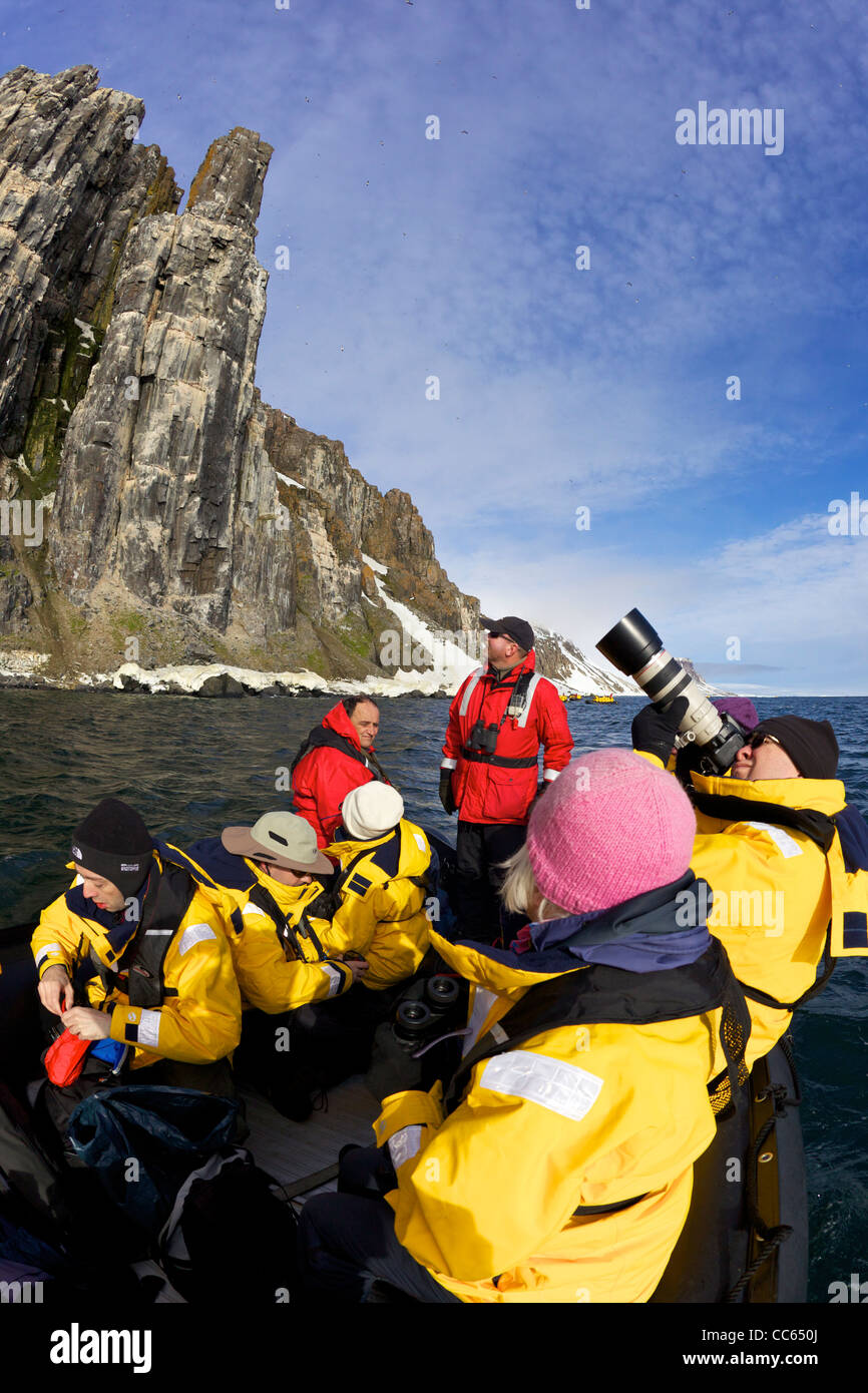Tourists on arctic adventure cruise in zodiac inflatables, Alkefjellet cliffs seabird colony in summer, Spitzbergen, - Stock Image